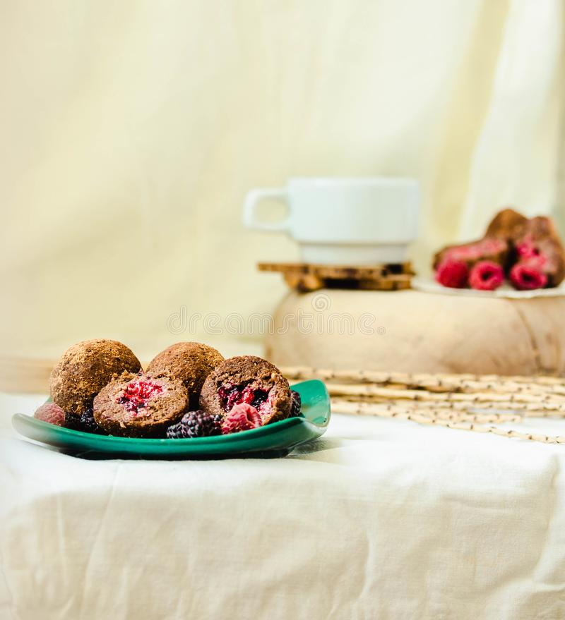 Homemade chocolate truffle with fresh raspberry in the green plate on white linen tablecloth backgound royalty free stock images