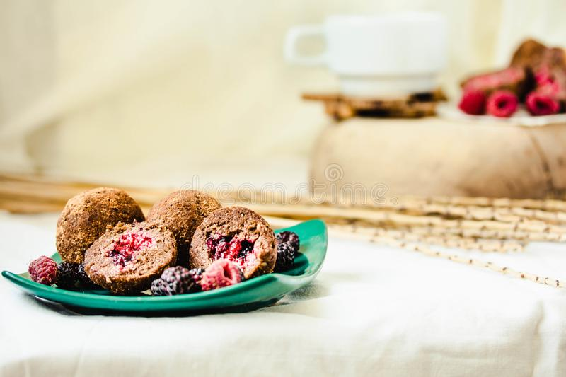 Homemade chocolate truffle with fresh raspberry in the green plate on white linen tablecloth backgound stock images