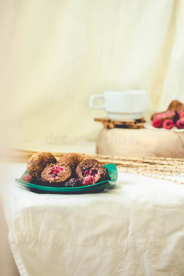 Homemade chocolate truffle with fresh raspberry in the green plate on white linen tablecloth backgound. Toning royalty free stock images