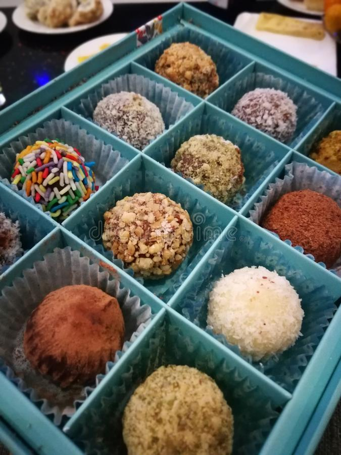 Homemade chocolates in a blue box, on top.set of candies of handwork.   candies in a box stock photography