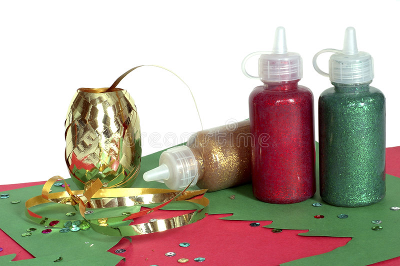 Homemade Christmas Cards. Ribbon, glitter glue, paper and sequence in process of making a Christmas Cards. Isolated on white stock photo