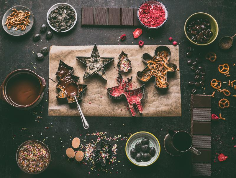 Homemade Christmas chocolate bars making. Christmas cutters with various toppings and flavorings. Melted chocolate in bowl. With spoon on dark rustic kitchen stock photos