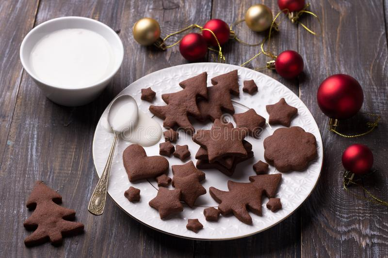 Homemade Christmas chocolate spiced cookies with sugar icing for decoration on a wooden table stock photos