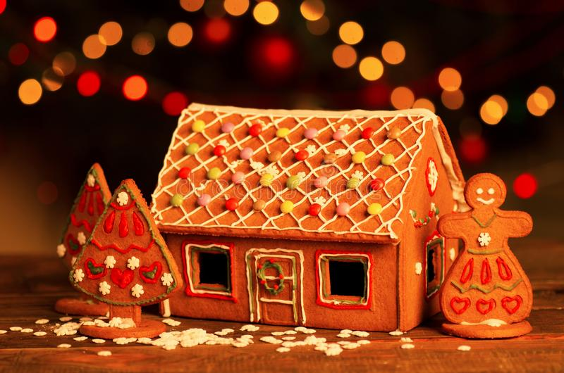 Homemade christmas gingerbread house on a table. Christmas tree lights on the background stock images