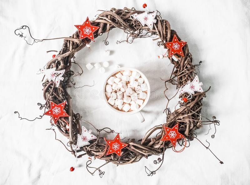 Homemade Christmas vine wreath with red wooden stars and hot chocolate with marshmallows on white background, top view. Copy space. Flat lay stock photos