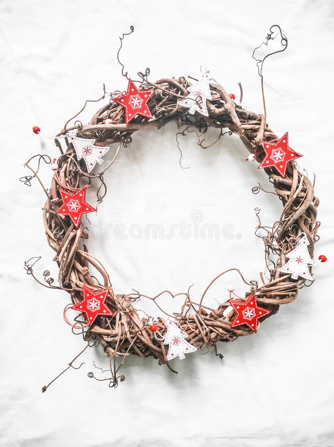 Homemade Christmas vine wreath with red wooden stars on white background, top view. Copy space royalty free stock image