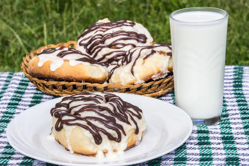 Download Homemade Cinnabons Cinnamon Buns With Cream Cheese Glaze And Chocolate Icing And  Glass Of Milk Stock Photo - Image: 83724663