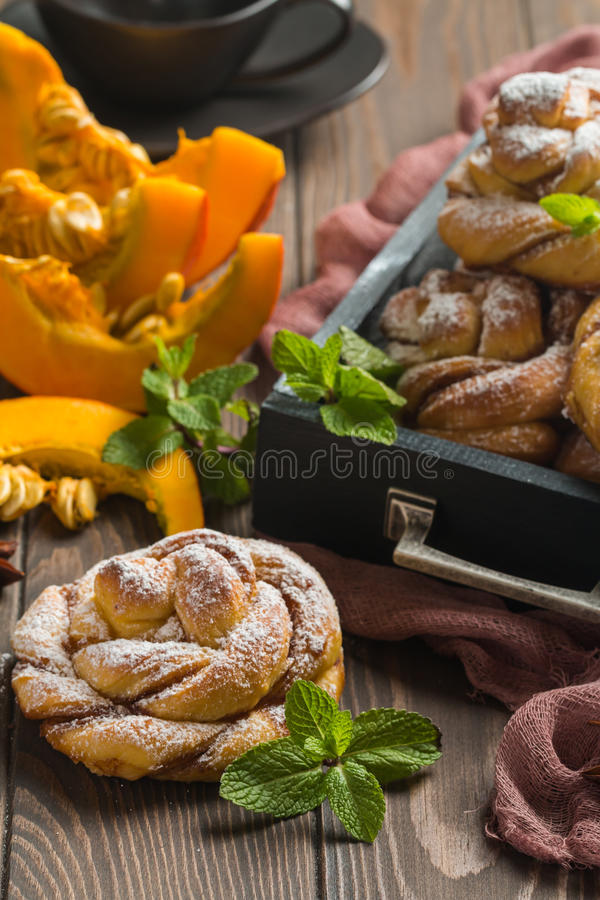Homemade cinnamon buns with pumpkin. Over wooden background royalty free stock photo