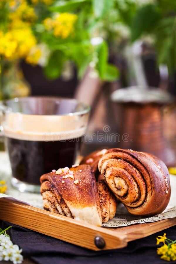 Homemade cinnamon and cardamom rolls and cup of black coffee royalty free stock images