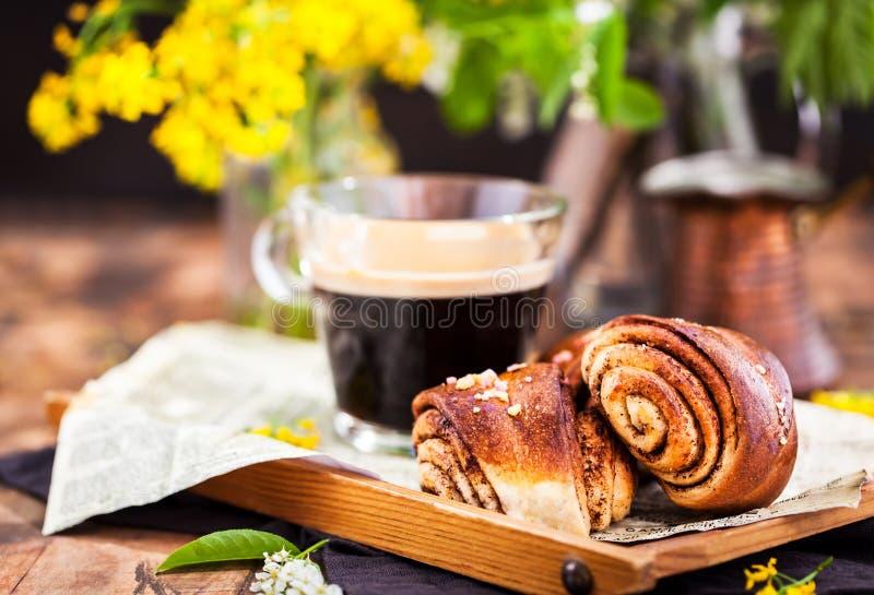 Homemade cinnamon and cardamom rolls and cup of black coffee stock photos