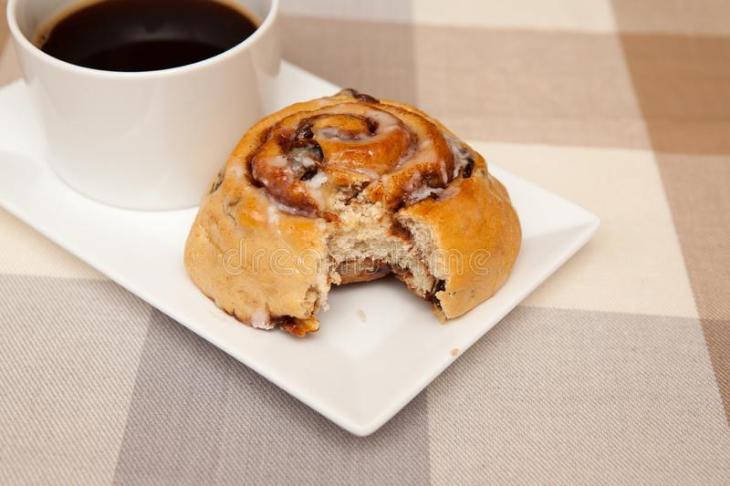 Homemade cinnamon swirls and a coffee. Homemade cinnamon swirl bread rolls on a plate with a cup of coffee royalty free stock image