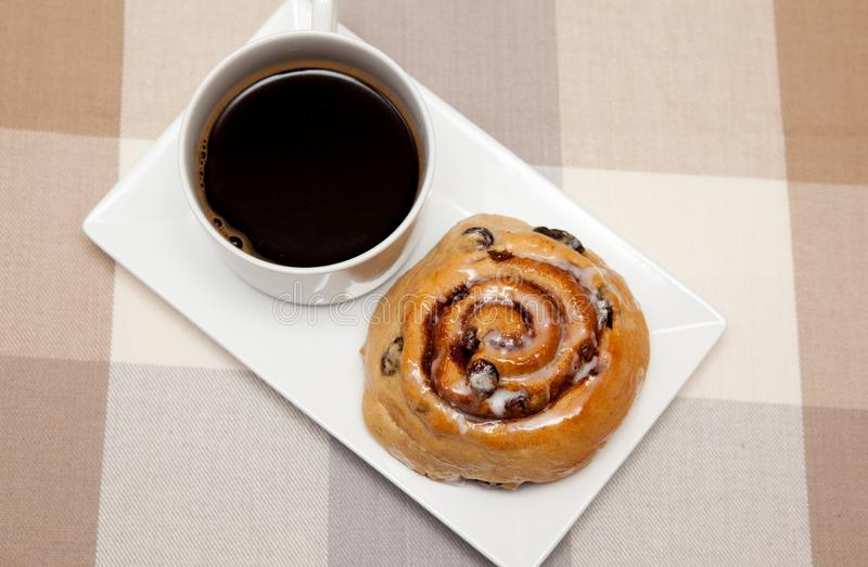 Homemade cinnamon swirls and a coffee. Homemade cinnamon swirl bread rolls on a plate with a cup of coffee royalty free stock images
