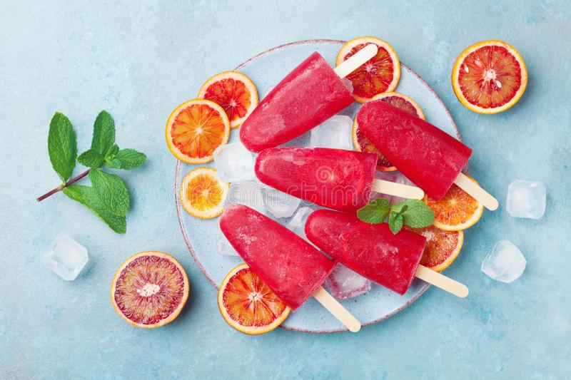 Homemade citrus ice cream or popsicles decorated mint leaves and orange slices on blue table top view. Frozen fruit juice. royalty free stock photo