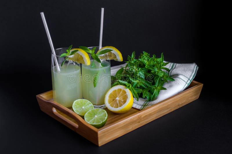 Homemade citrus lemonade in glasses with straws with mint leaves and a bunch of mint, lemons, limes on a bamboo tray royalty free stock photography