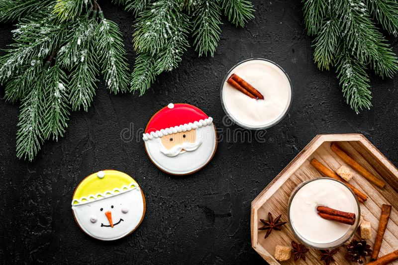 Homemade classic eggnog with cinamon and badian near spruce branch, pinecones, gingerbread on black background top view stock photos