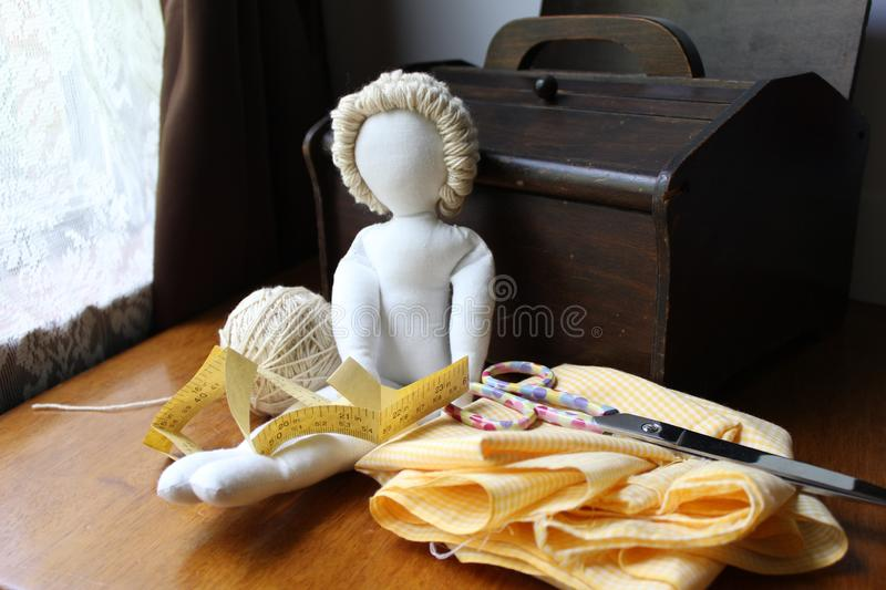 Homemade cloth rag doll with sewing supplies royalty free stock photos