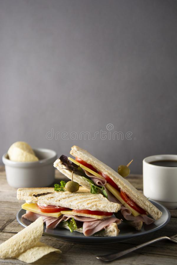 Homemade club sandwich. Toasted white bread triangles with ham, cheese fresh vegetables. Wooden table royalty free stock photos
