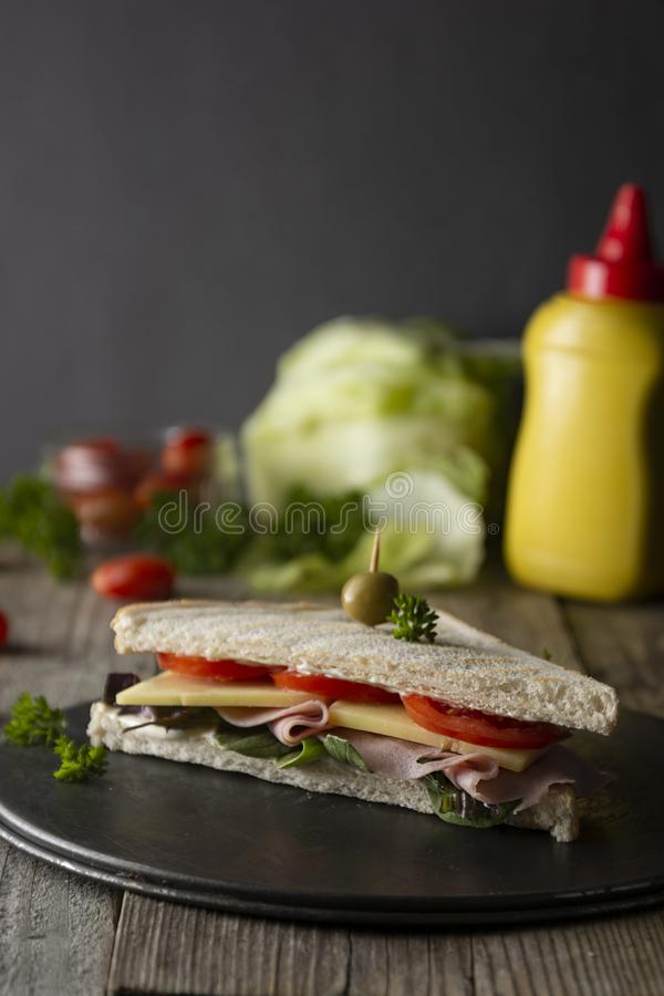 Homemade club sandwich. Toasted white bread triangles with ham, cheese fresh vegetables. Wooden table stock photography