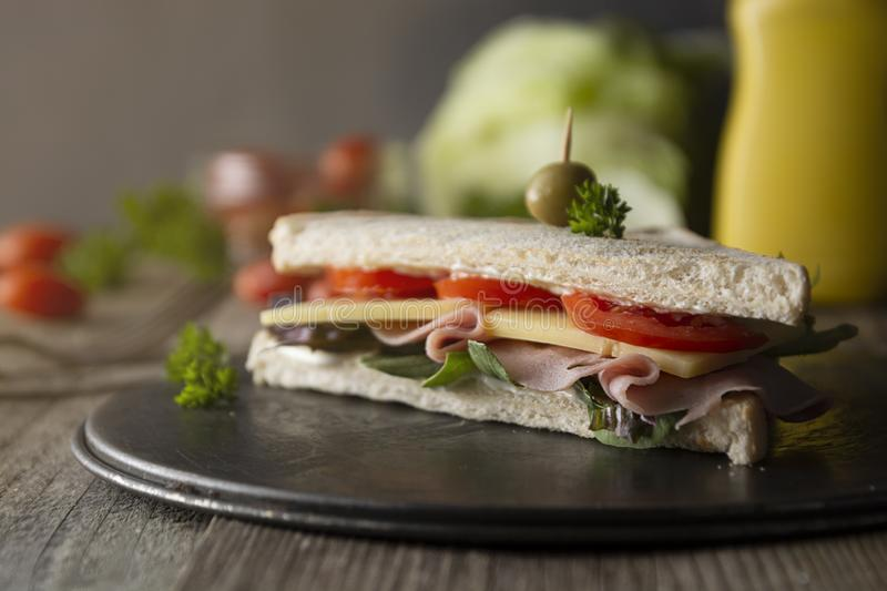 Homemade club sandwich. Toasted white bread triangles with ham, cheese fresh vegetables. Wooden table royalty free stock images
