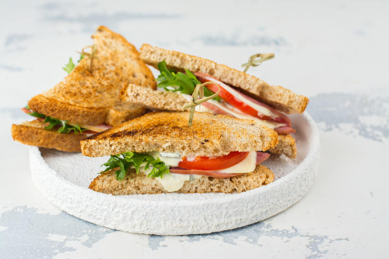 Homemade club sandwiches. Delicious homemade club sandwiches with ham, cheese and vegetables. Tasty breakfast or lunch concept. Copy space royalty free stock image