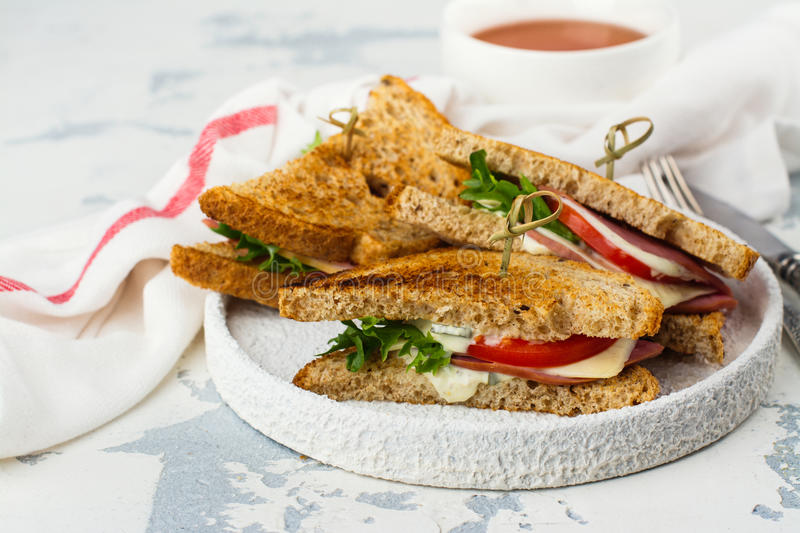 Homemade club sandwiches. Delicious homemade club sandwiches with ham, cheese and vegetables. Tasty breakfast or lunch concept royalty free stock photography