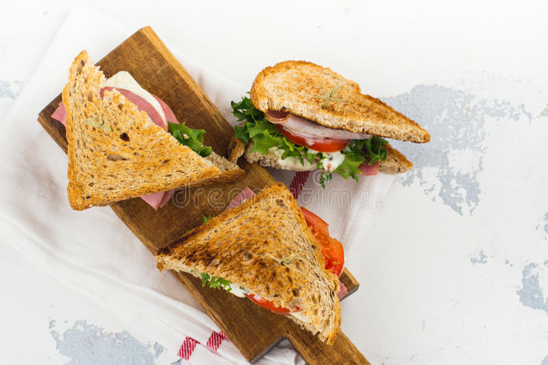 Homemade club sandwiches. Delicious homemade club sandwiches with ham, cheese and vegetables. Tasty breakfast or lunch concept stock images