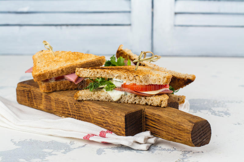 Homemade club sandwiches. Delicious homemade club sandwiches with ham, cheese and vegetables. Tasty breakfast or lunch concept stock photography