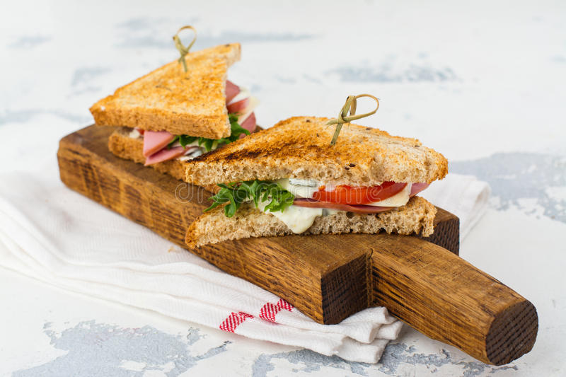 Homemade club sandwiches. Delicious homemade club sandwiches with ham, cheese and vegetables. Tasty breakfast or lunch concept. Copy space stock images