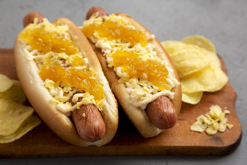 Homemade colombian hot dogs with pineapple sauce, chips and mayo ketchup on a rustic wooden board on a gray background. Flat lay,. From above, top view. Close royalty free stock photos