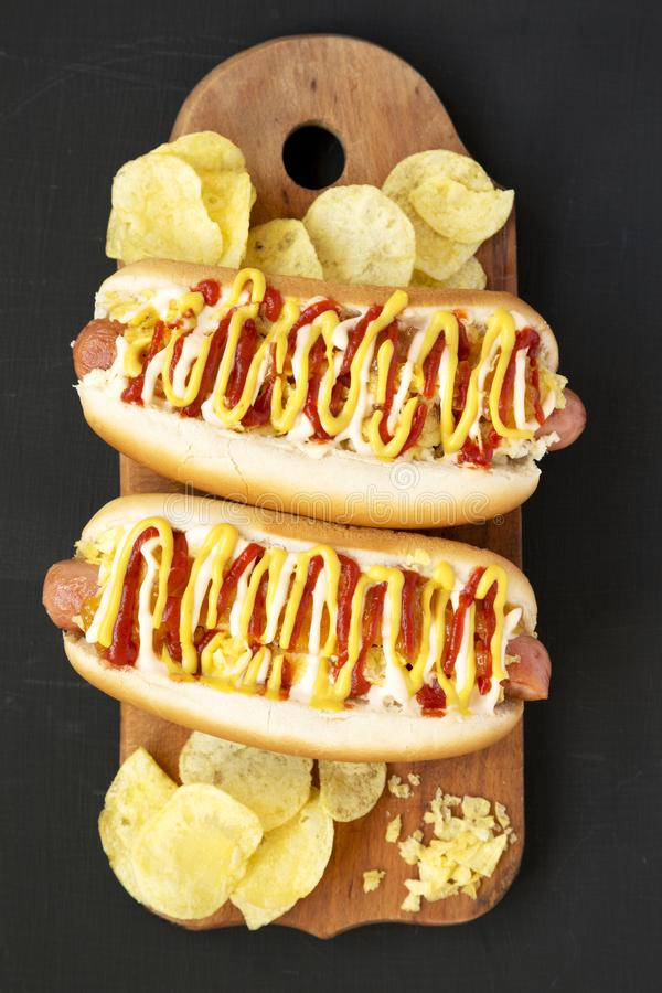 Homemade colombian hot dogs with pineapple sauce, yellow mustard and mayo ketchup on a rustic wooden board on a black table. Flat. Lay, from above, top view royalty free stock photo