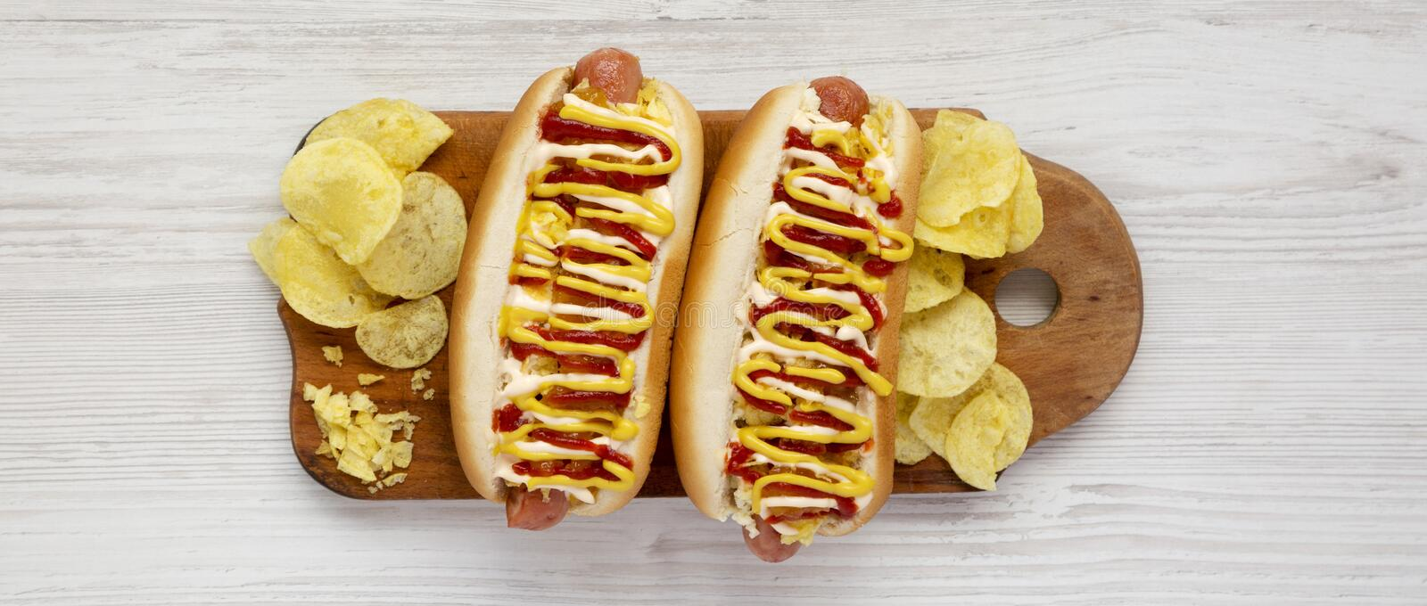 Homemade colombian hot dogs with pineapple sauce, yellow mustard and mayo ketchup on a rustic wooden board. Flat lay, from above,. Top view. Close-up stock images