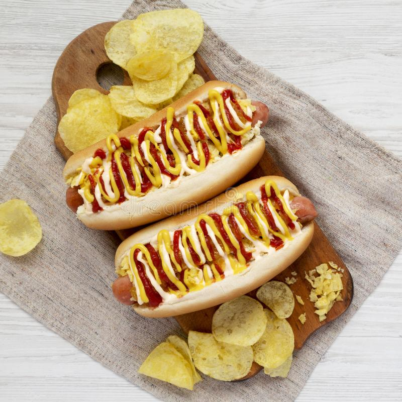 Homemade colombian hot dogs with pineapple sauce, yellow mustard and mayo ketchup on a rustic wooden board. Flat lay, from above,. Overhead. Close-up stock photos