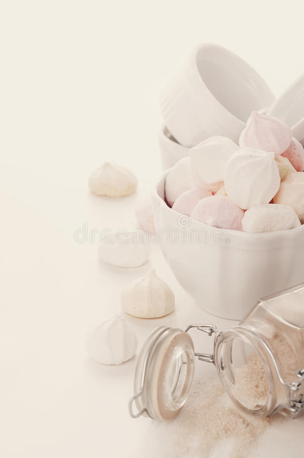 Homemade colored meringue, sugar and eggs. French meringue cookies on white wooden background .Toned photo stock photography