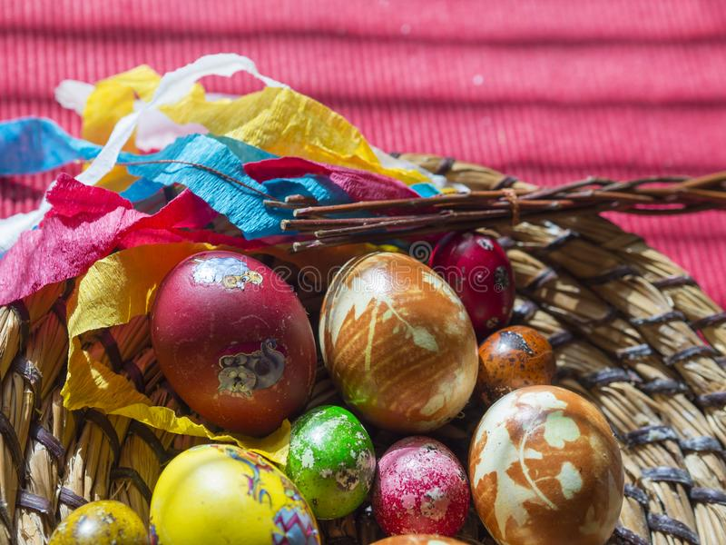 Homemade Colorful Painted easter eggs in straw flat basket with easter stickers and Pomlazka - czech traditional braided royalty free stock images