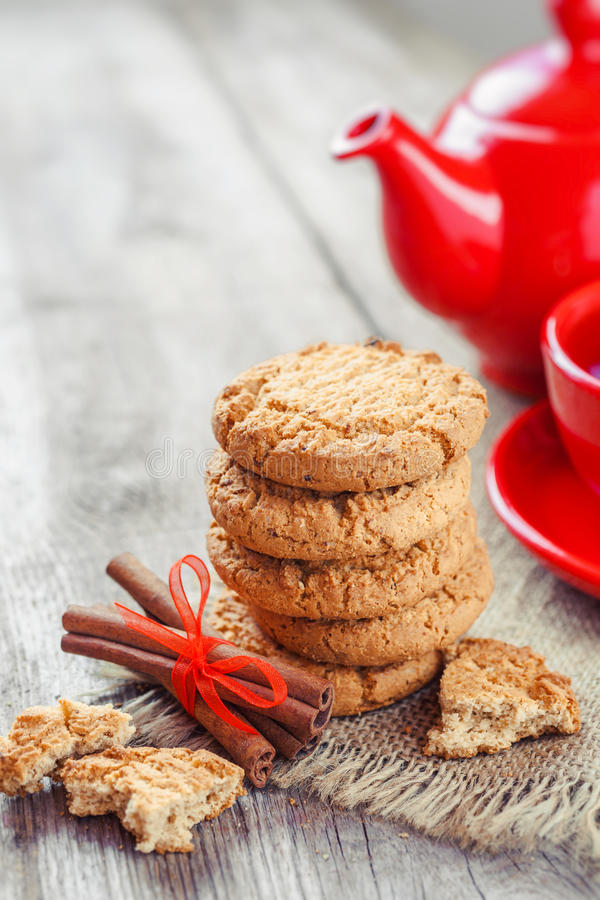 Homemade cookies, cinnamon sticks, red teakettle and tea cup. On old table stock photos