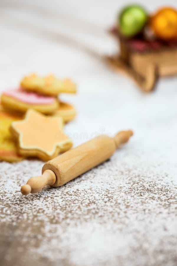 Homemade cookies, dough roll and slate with christmas balls on icing sugar. Seasonal greeting card stock photography