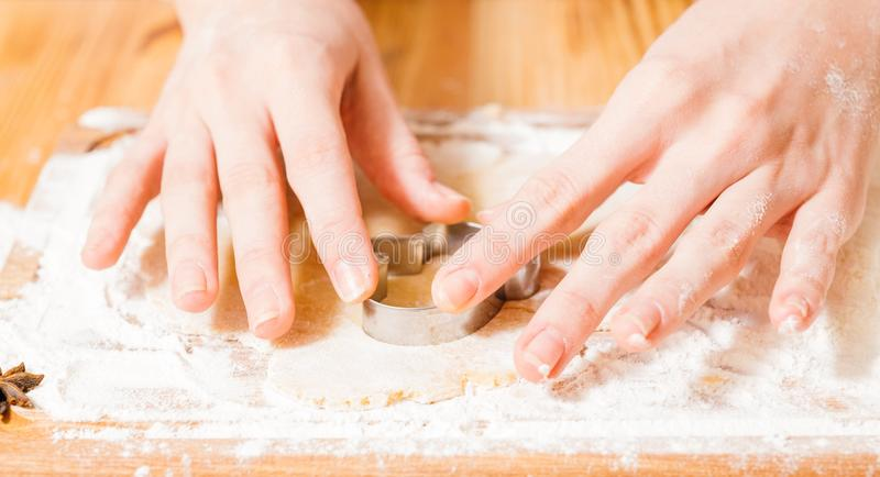 Homemade cookies recipe dough gingerbread biscuits. Homemade cookies recipe. Closeup of woman hands cutting dough, making gingerbread biscuits royalty free stock images