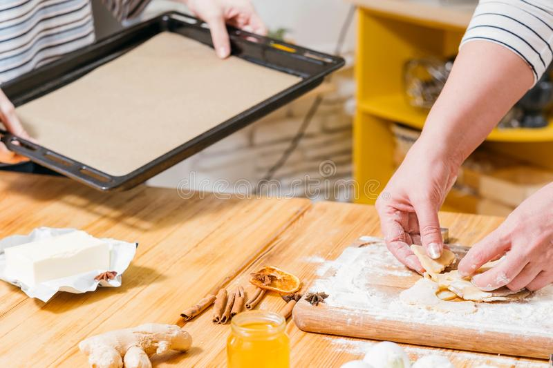 Homemade cookies recipe gingerbread biscuits. Homemade cookies recipe. Cropped shot of women using sheet pan to bake gingerbread biscuits stock photo