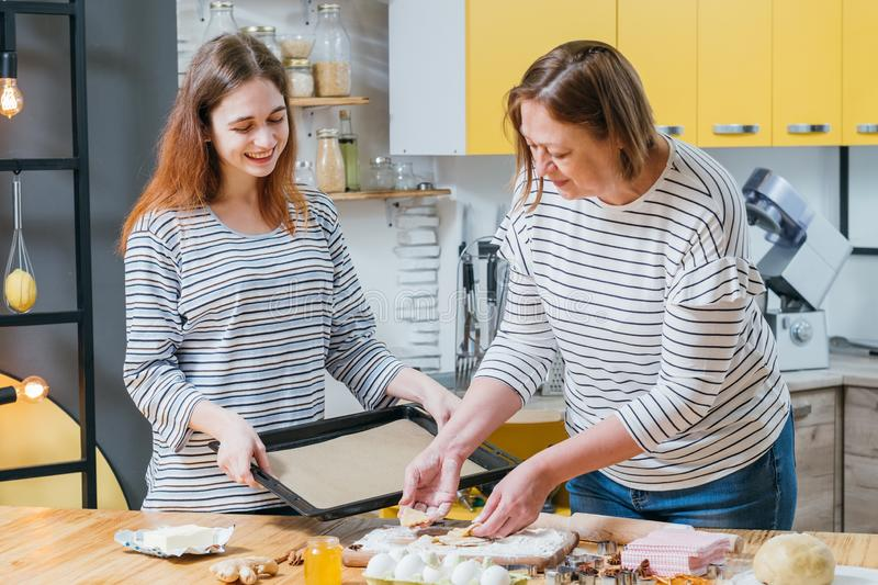 Homemade cookies recipe gingerbread biscuits. Homemade cookies recipe. Daughter helping mother to cook, holding sheet pan for gingerbread biscuits stock photo