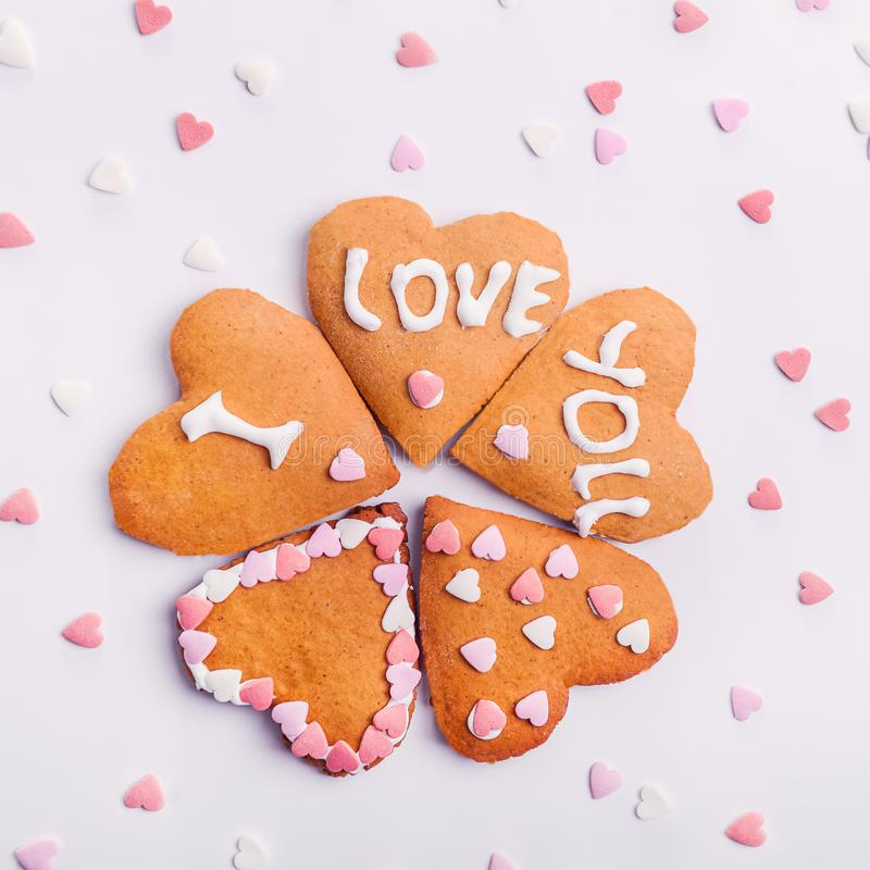 Homemade cookies in the shape of heart with letteing I Love You with sweets sugar candy hearts on the white background. Valentine royalty free stock images