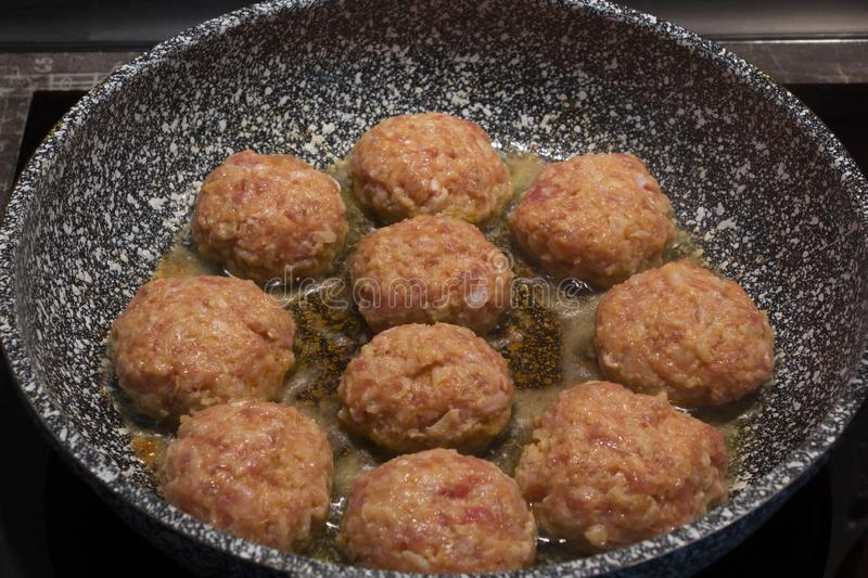 Homemade cooking cutlets in a grey granite frying pan royalty free stock images