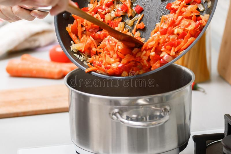 Homemade cooking. A woman from the pan adds fried vegetables to the Stock pot. Close-up.  stock photos