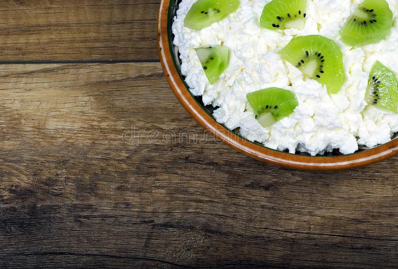 Homemade cottage cheese in a bowl on wooden table. royalty free stock photo