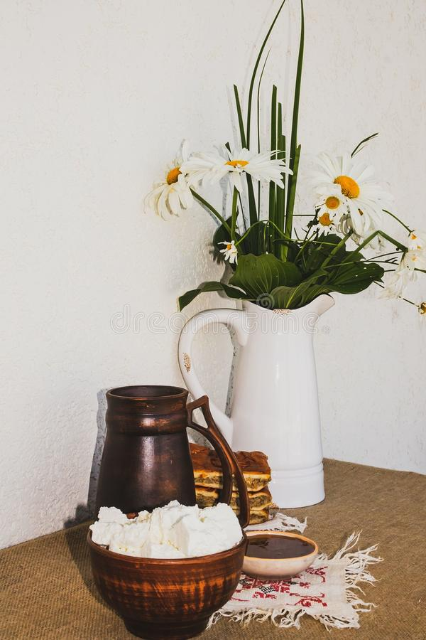 Homemade cottage cheese, honey, pie, a jug of milk and a jug with a bouquet of chamomiles. stock photo