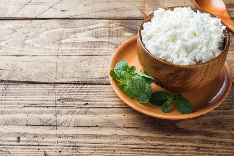 Homemade cottage cheese with mint in a bowl on old wooden table. Copy space. Homemade cottage cheese with mint in a bowl on old wooden table Copy space royalty free stock images