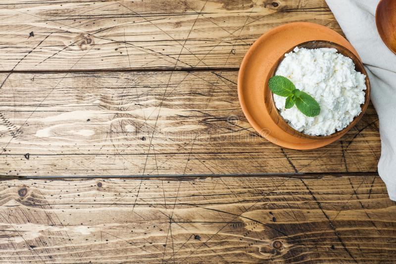 Homemade cottage cheese with mint in a bowl on old wooden table. Copy space. Homemade cottage cheese with mint in a bowl on old wooden table Copy space royalty free stock photos