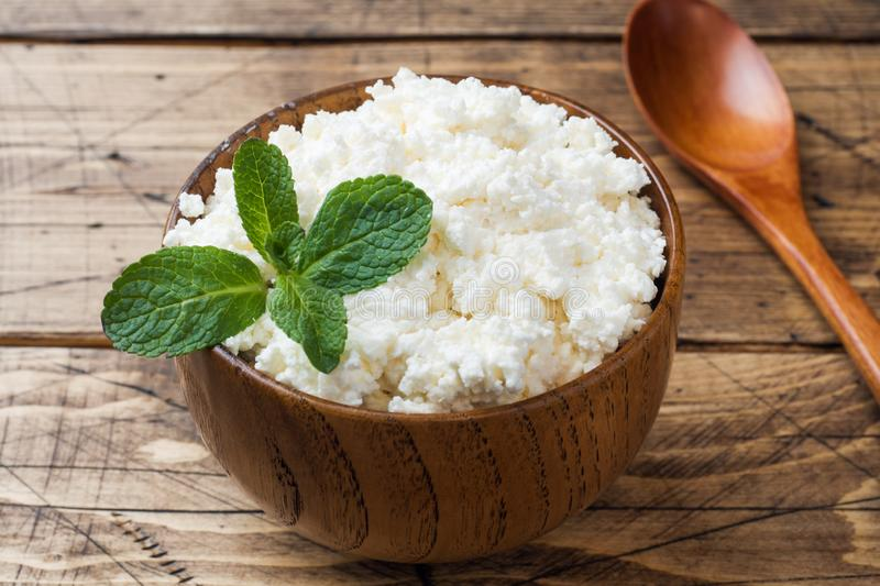 Homemade cottage cheese with mint in a bowl on old wooden table.  royalty free stock photo