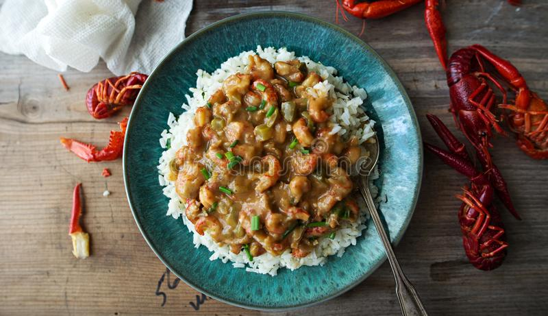 Homemade crawfish etouffee on a blue plate. Shown with whole boiled crawfish on a wood background. Directly overhead, copy space. Etouffee made with a blond royalty free stock photos