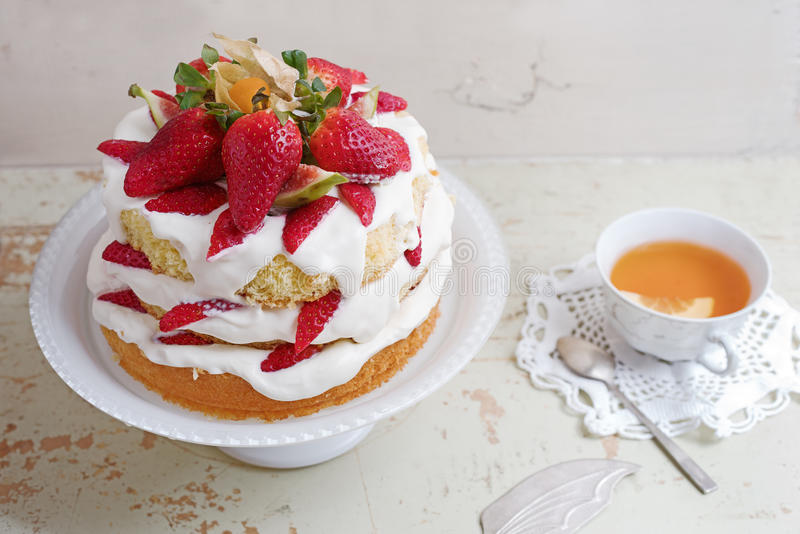 Homemade cream layer cake, fresh, colorful, and delicious dessert with juicy strawberries, sweet whipped cream and cream cheese. Selective focus. Space for royalty free stock photos