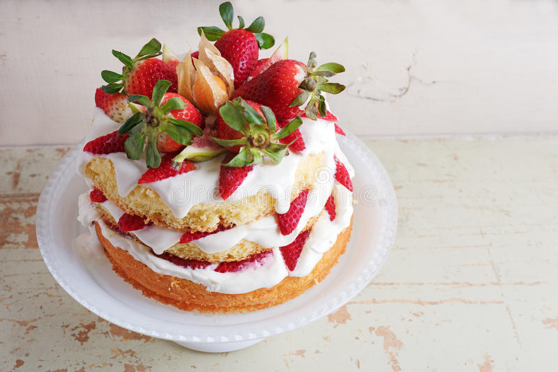 Homemade cream layer cake, fresh, colorful, and delicious dessert with juicy strawberries, sweet whipped cream and cream cheese. Selective focus. Space for royalty free stock images